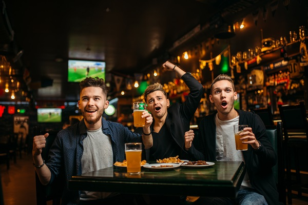 Three young men celebrates game victory in a sport bar, happy friendship of football fans